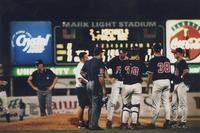 Players and coach gather around the pitcher's mound